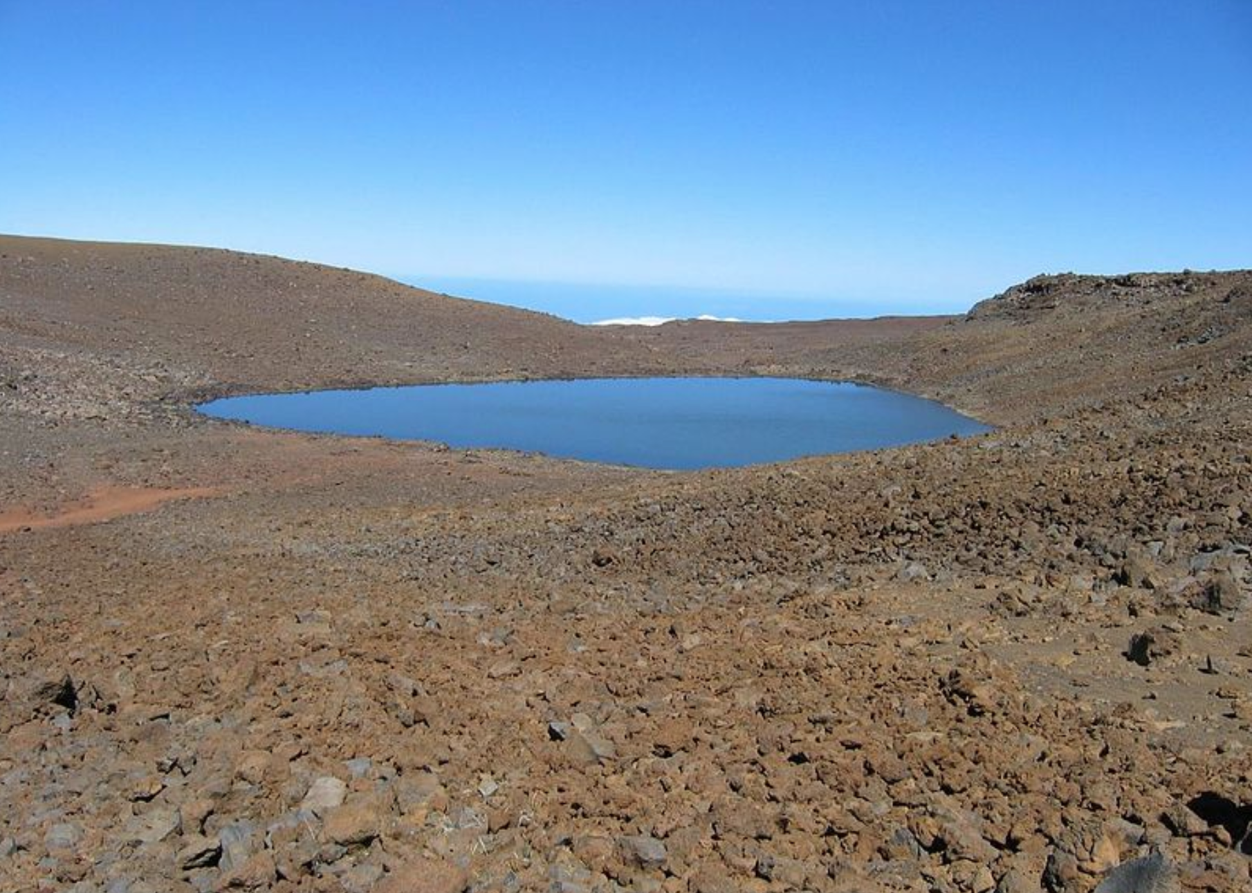 Slide 47 of 52: One of the few lakes in Hawaii, Lake Wa'ia'u is located inside the cinder cone of the dormant volcano Mauna Kea. The contrast between its blue water and the unforgiving volcanic landscape that surrounds it is stunning.