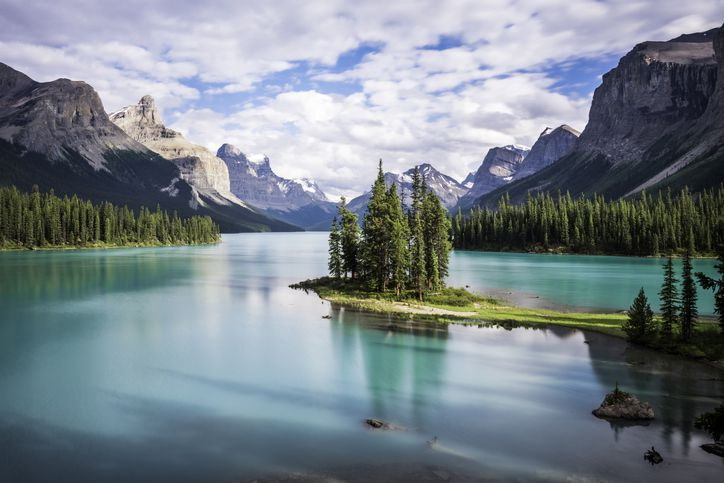 Slide 49 of 52: Maligne Lake is another alpine lake—this one located in Alberta's Jasper National Park—that boasts vivid turquoise waters that reflect the jagged glaciers around them.
