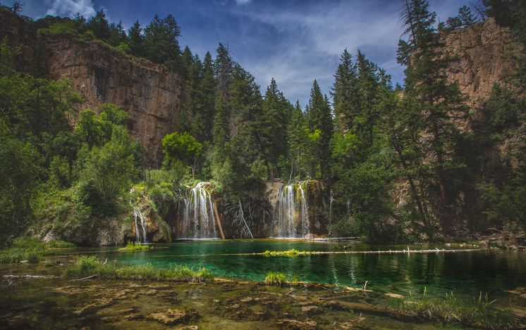 Slide 22 of 52: Crystal-clear Hanging Lake, in Glenwood Canyon, is a travertine lake fed by waterfalls. The delicate landscape is visited in summer, but can be dangerous in winter.