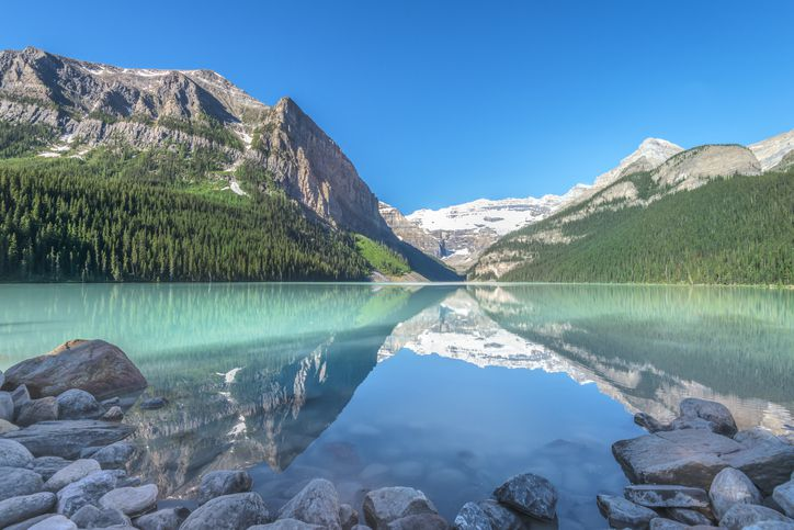 Slide 19 of 52: Glacier-fed Lake Louise is a milky turquoise, and the surrounding mountains—as seen from luxury hotel Fairmont's Chateau Lake Louise—make the alpine lake impossibly gorgeous.