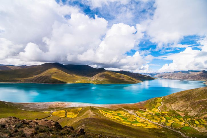 "Slide 4 of 52: Yamdrok (which means ""turquoise"" in English) is a sacred lake to Tibetans. The long, slender body of water is surrounded by a beautifully austere landscape of hills and snow-capped mountains."