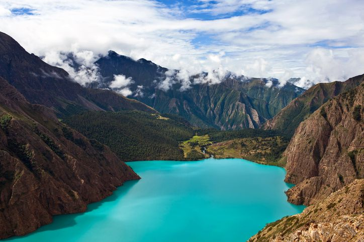 Slide 29 of 52: Located in Nepal's spectacular Shey Phoksundo National Park in the Himalayas, Phoksundo Lake's brilliant turquoise waters are surrounded by jagged glacial mountains.