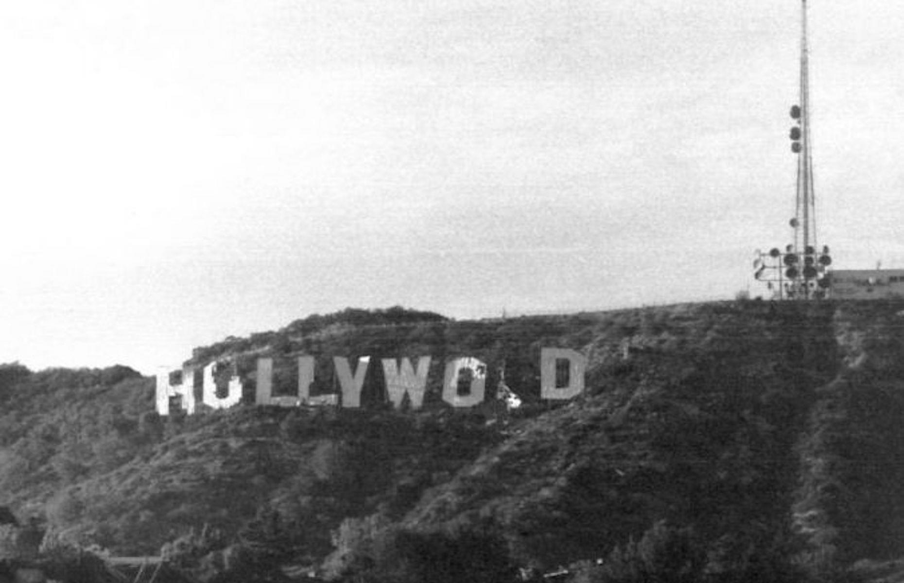"""Slide 15 of 48: Erected in 1923 as a temporary advertisement for a real estate development, the Hollywood sign is now one of the most famous in the world. It originally read Hollywoodland but the """"land"""" was removed when it was restored in 1949. The landmark, which sits on the southern side of Mount Lee in Griffith Park, officially became a historic monument in the 1970s (pictured here) and the deteriorating structure was restored once again in 1978 on the back of a campaign led by Playboy founder Hugh Hefner."""
