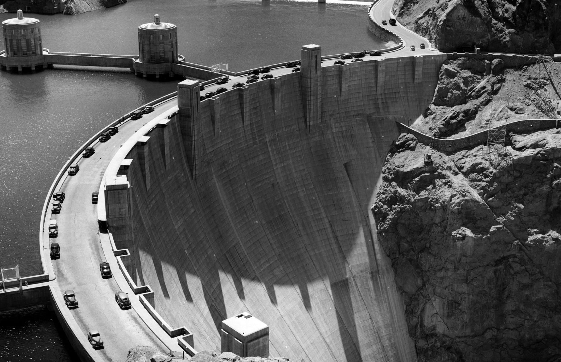 Slide 19 of 48: Built between 1931 and 1936, during the Great Depression, to tame the Colorado River, the mighty Boulder Dam on the Arizona-Nevada border was the largest in the world. Its reservoir Lake Mead remains the largest in the world. It opened for tours in 1937 and became a popular tourist destination. It was officially renamed the Hoover Dam by the then-president, Herbert Hoover, in 1947. It was designated a National Historic Landmark in 1985 and a new visitor center was built in 1995.