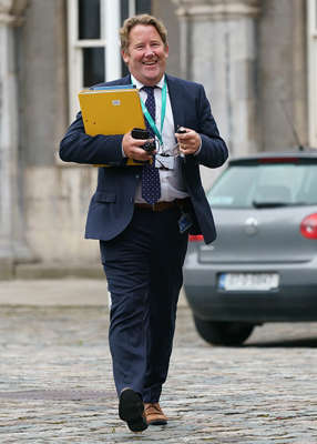 a man wearing a suit and tie talking on a cell phone: Minister O'Brien said that he had made the decision to cancel yesterday, as he didn't want media commentary to 'detract' from a housing announcement, which he said will happen next month.. Pic: Fran Veale