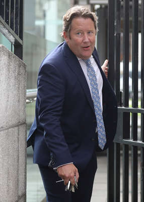 a man wearing a suit and tie talking on a cell phone: The cases – which further highlight the toothlessness of the housing watchdog – were identified by the RTB in an analysis sent to the Minister for Housing Darragh O'Brien in July. Pic: Leah Farrell/RollingNews.ie