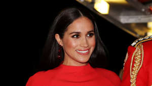 Meghan Markle wearing a hat and smiling at the camera