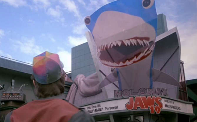 Slide 5 de 11: Em outro momento, já explorando a Hill Valley do futuro, Marty se depara com um cinema que está exibindo Tubarão 19! Além da brincadeira de que o clássico filme teria várias continuações, o personagem principal se depara com um tubarão literalmente vindo em sua direção. Qual tecnologia é essa? 3D!