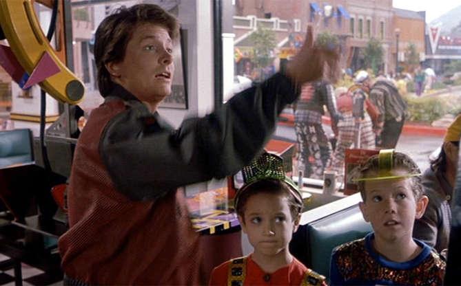 Slide 2 de 11: A começar pelo videogame. Quando Marty entra em um café, já em 2015, ele se depara com dois garotinhos tentando ligar um jogo do tipo fliperama. Quando Marty começa a apertar botões e a atirar, os meninos ficam menos empolgados, já que é necessário usar as mãos para jogar! Hoje, por exemplo, temos acesso aos jogos em que ficamos na frente da televisão e mexemos braços, dançamos, etc.