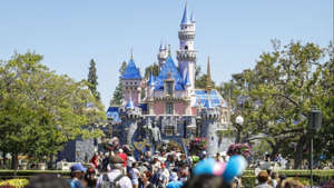 a group of people walking in front of a crowd: Many locals have gotten used to visiting Disneyland daily, weekly or monthly. (Jay L. Clendenin / Los Angeles Times)