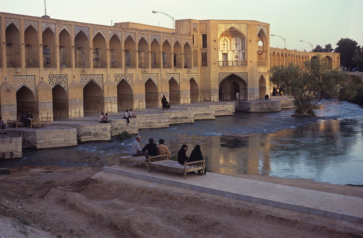 Slide 29 of 31: This photo from 1989 shows the Khaju Bridge on the Zayanderud Riber, which is known as the finest bridge in Iran. It was built on top of an older bridge around 1650, consists of 23 stone arches, and is about 430 feet long and nearly 40 feet wide.