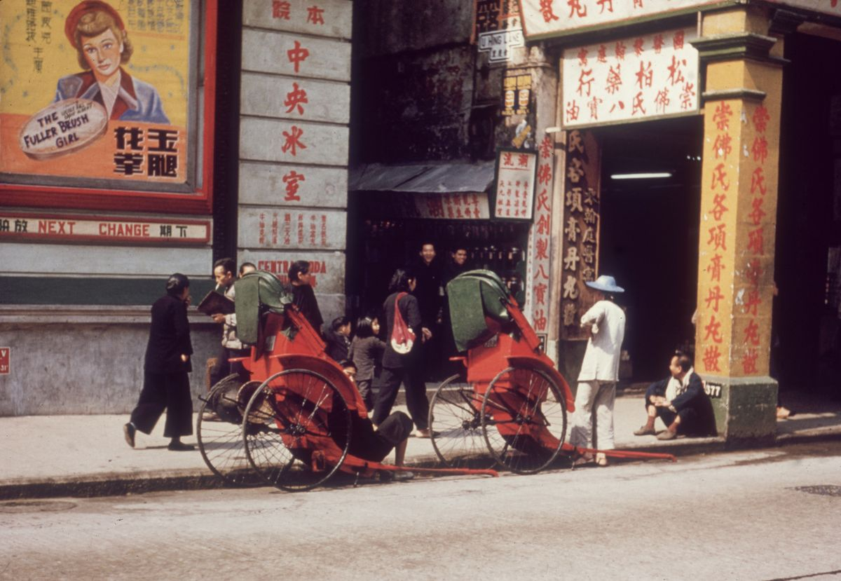 """Slide 16 of 31: The rickshaw may have originated in Japan, but it has been a staple of culture in Hong Kong as well. The name, jinrikisha in Japanese, means """"man-powered carriage."""" Here, you can see one in Hong Kong from 1955."""
