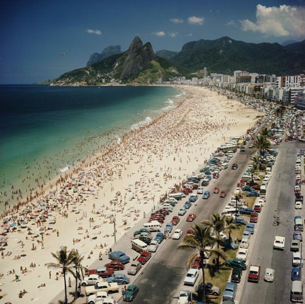Slide 6 of 31: Ipanema Beach, pictured here in 1960, has long been one of the most popular beaches in Rio de Janiero. The neighborhood in the area was traditionally more wealthy than the neighborhood in Copacabana, making the beach more refined, and in the 1970s, it became a major spot for surfers.