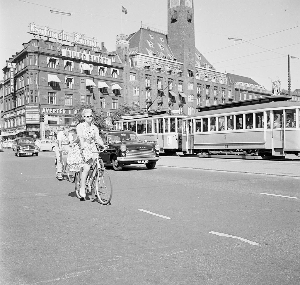 """Slide 17 of 31: Copenhagen is the capital of Denmark and the largest city in Scandinavia. It began as a small fishing village and was once called """"Havn,"""" which means harbor. In 1343, King Valdemar Atterdag made Copenhagen the capital of Denmark. This photo from 1960 shows a girl riding her bicycle down the street."""