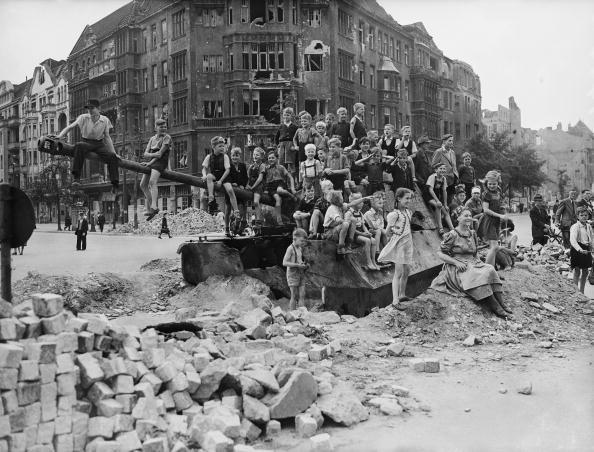 Slide 25 of 31: Berlin was left in ruins after World War II, when Soviet forces came in and fighting began. After the war, the city was occupied by Allies, and civilians began cleaning it up. In this photo from 1945, you see German children playing on a tank in one area of the city that was severely damaged by bombs.