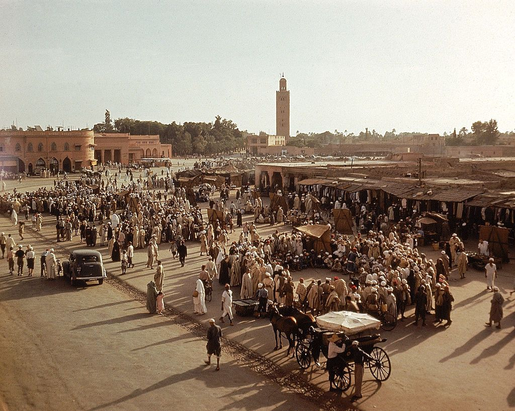 Slide 28 of 31: This photo from 1950 shows an older Djemaa-El-Fna, which is the main square and market in Marrakesh. It's there that you'll find everything from fortune tellers and snake chamers to poets and shops. It dates back to the founding of Marrakesh by the Almoravids in 1062 and has been used as a market and gathering place for over a thousand years.