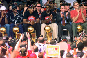 Dennis Rodman, Richard M. Daley, Phil Jackson in front of a crowd posing for the camera: Dennis Rodman, Scottie Pippen, Michael Jordan and coach Phil Jackson are joined on stage by Chicago Mayor Richard Daley, second from right, during a city-wide rally to celebrate the Bulls' sixth championship in 1998.
