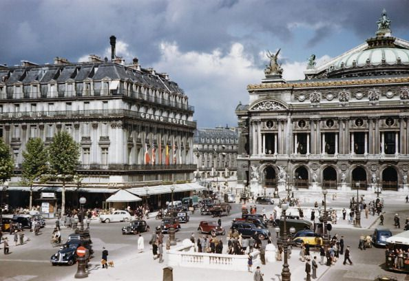 Slide 3 of 31: The iconic Grand Hotel in Paris dates back to 1862, when Empress Eugenie inaugurated it. The Palais Garnier (the Opera) dates back even further, to 1669. The two structures stand next to each other, and as you can see in this photo from 1960, it's a popular tourist destination.