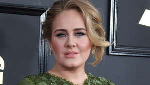 Adele smiling in front of a window