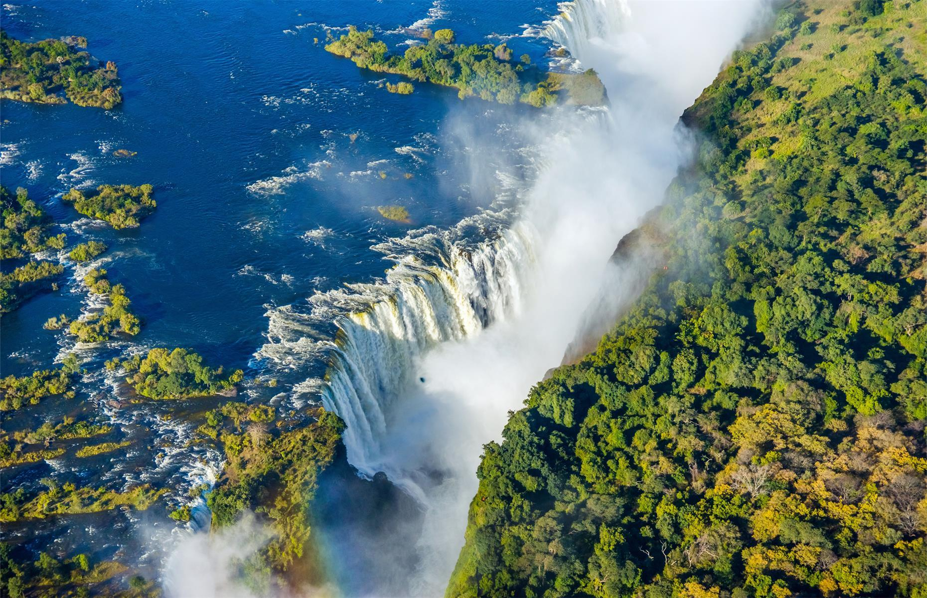 """Slide 19 of 51: Known as Mosi-oa-Tunya (""""the smoke that thunders"""") in the local language, this thundering curtain of water on the Zambia and Zimbabwe border is classed as the largest waterfall in the world, based on its width. At a whopping 5,604-foot-wide (1,708m) and 354-foot-long (108m), it's a striking reminder of the power of nature. There's also Devil's Pool, a little pocket of water on the edge of the abyss and a popular swimming spotfor thrill-seekers. See more incredible images of the beautiful and terrifying power of Mother Nature here."""