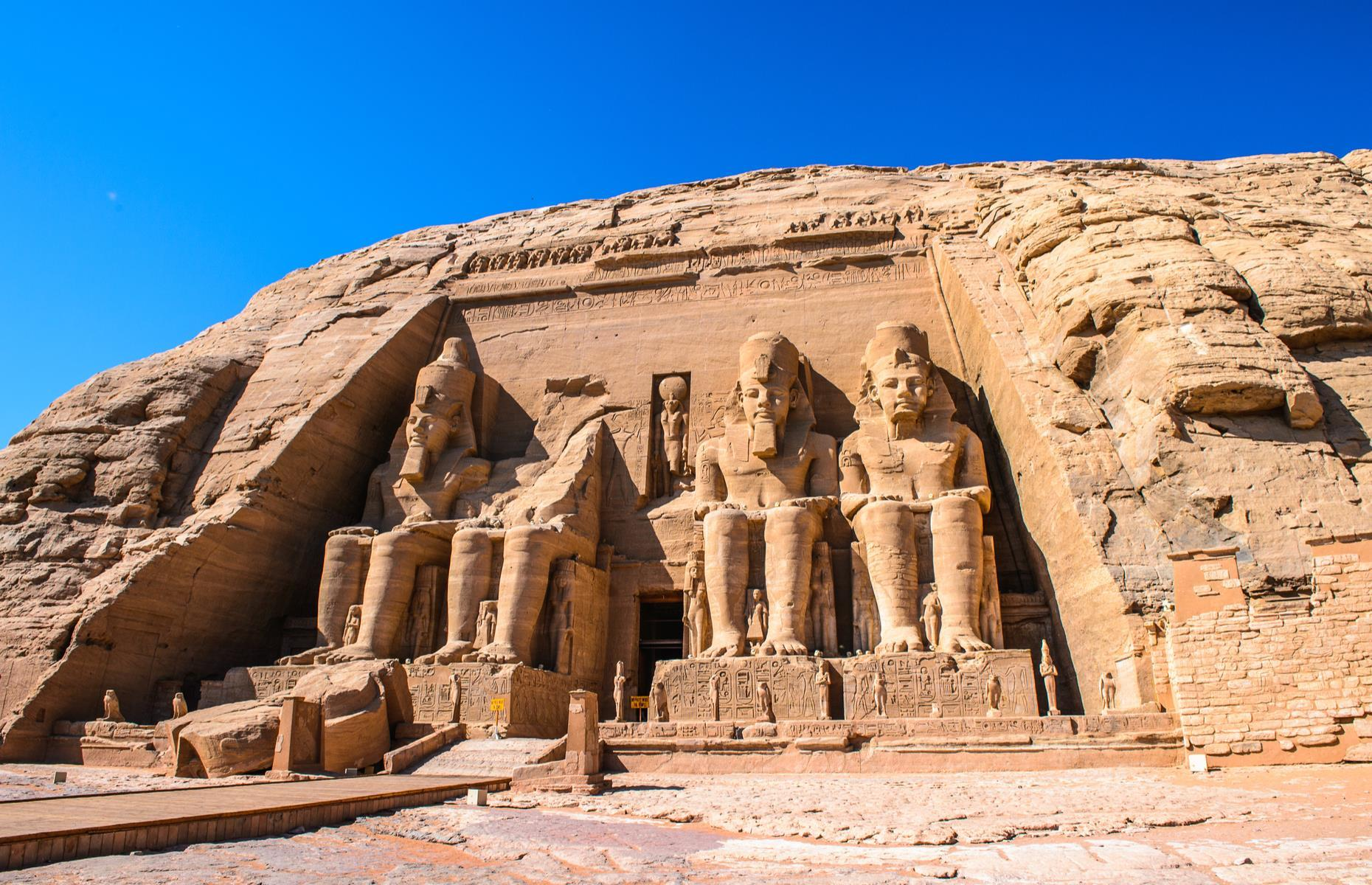 Slide 30 of 51: Painstakingly chipped into a mountainside, this imposing temple was completed in 1265 BC to commemorate the victory of Ramesses II and his queen Nefertari in the Battle of Kadesh. Set in the deep south of Egypt, it is most famous for its 65-foot-high (20m) depictions of the powerful pharaoh.The mighty rock-hewn temple lay forgotten until it was rediscovered by Swiss traveler Johann Ludwigin 1813. When the Aswan Damwas built during the 1960s, the templewas carefullydismantled and moved to higher ground to save it from flooding. Today, the mighty monumentlooms safely inits remote location.