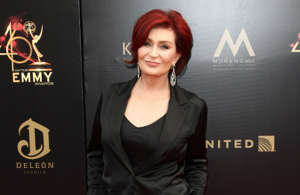 Sharon Osbourne holding a sign posing for the camera