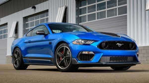 a blue car parked in front of a building: 2021 Ford Mustang Mach 1
