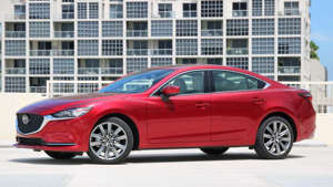 a car parked in front of a building: 2019 Mazda6 Signature Pro/Con