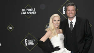 Gwen Stefani, Blake Shelton holding a sign posing for the camera