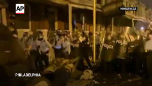 a group of people standing in front of a store: Protesters square off with police in Philadelphia