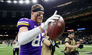 a person holding a baseball bat: Kyle Rudolph celebrates after game-winning touchdown.