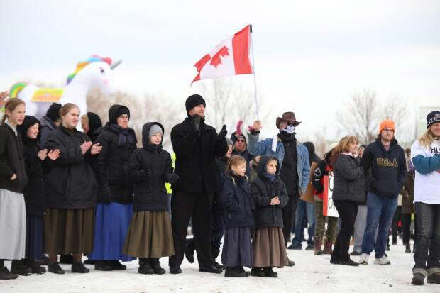 a group of people standing in front of a crowd posing for the camera: Protesters were not wearing protective masks, nor physically distancing. Some protesters, like the man holding an upside-down Canada flag, wore masks to obscure their faces.