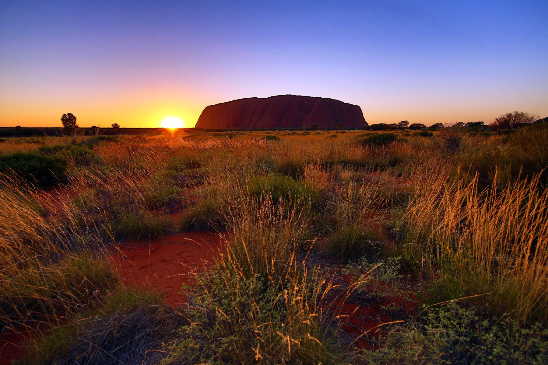 Slide 20 of 31: The majestic red-rock formations in this park are particularly impressive at sunrise and sunset. They can be admired from various viewpoints at these times. This is a sacred site for the region's Indigenous population, the Anangu, who manage the park in partnership with the state. Visitors can see rock art dating back tens of thousands of years, testament to Anangu ancestral education.