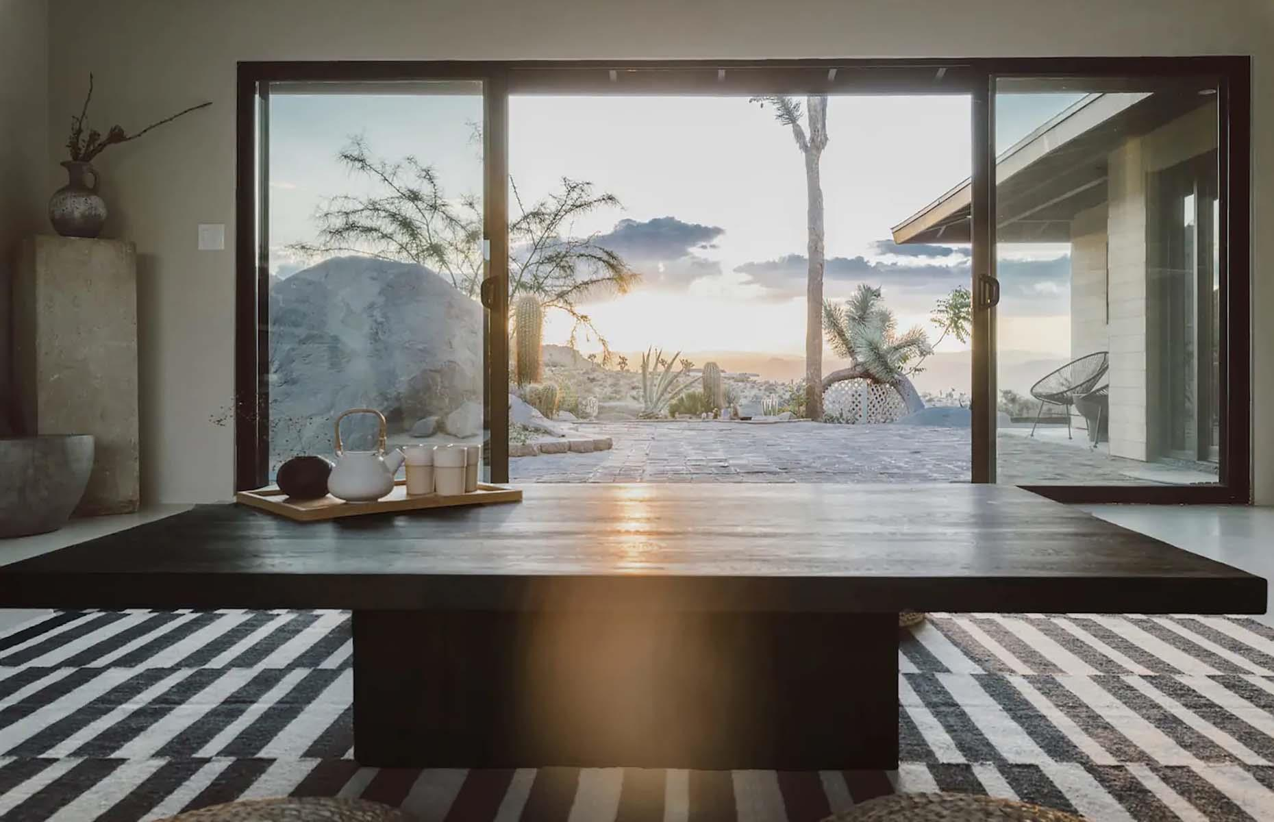 Slide 3 of 31: Surrounded by the truly unique landscape of Joshua Tree, Villa Kuro fits seamlessly into its surroundings. Originally built in the 1960s, the ranch-style house has been restored and transformed into a relaxing hideaway, framing the desert views with floor-to-ceiling picture windows. The property is located in front of an ancient boulder mountain and at night there are stargazing opportunities aplenty, either from the firepit area or the salt water hot tub. The entrance to Joshua Tree National Park is just a 10-minute drive away.