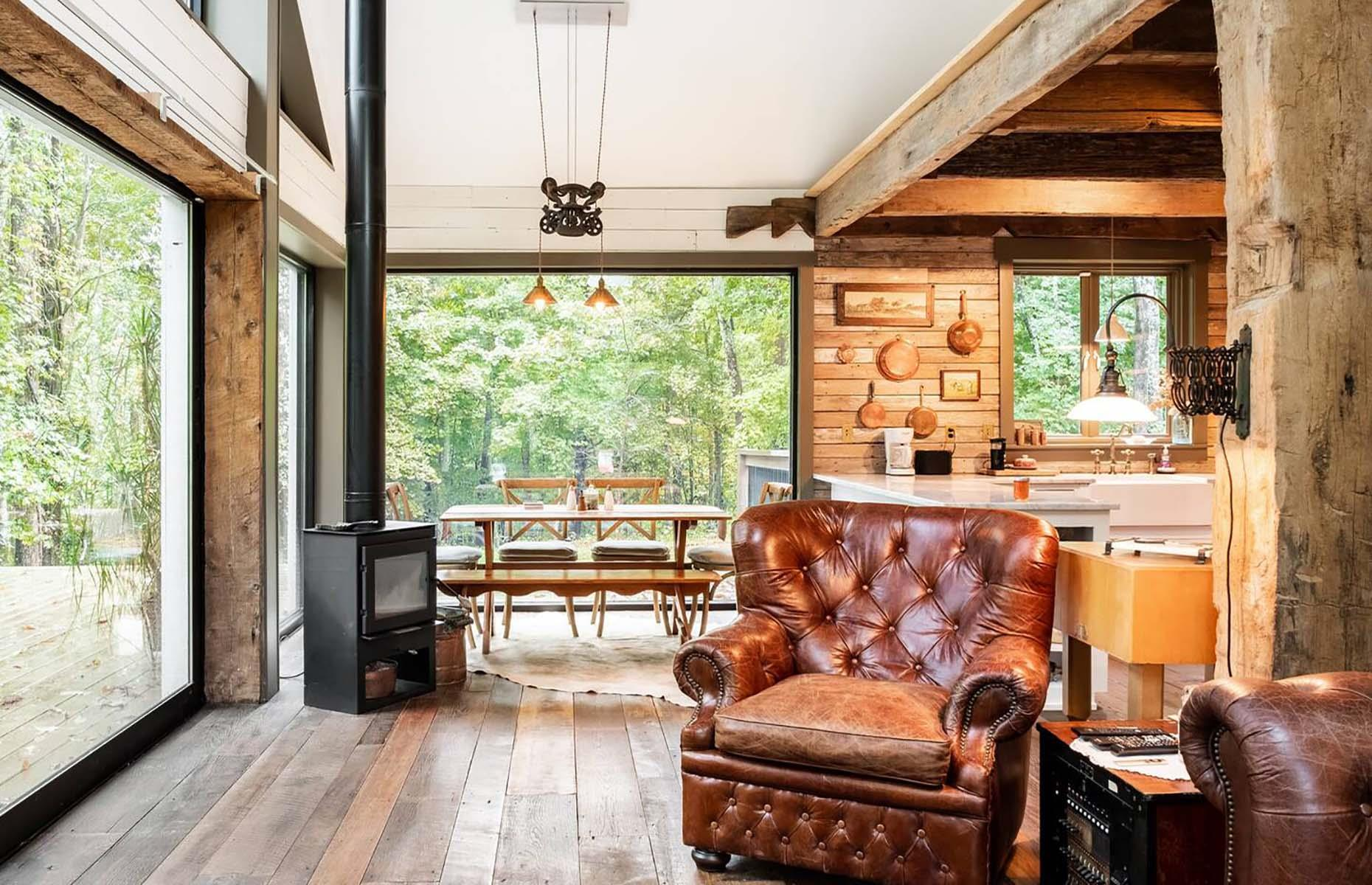 Slide 5 of 31: Made from recycled materials, this cozy cabin near Nashville is the ultimate secluded getaway. Hugged by the surrounding forest, the open-plan home has a vintage feel to it. Thanks to the floor-to-ceiling picture windows, you can drink in the area's natural beauty from the comfort of an armchair.