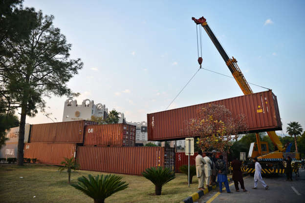 Slide 1 of 144: Truck drivers stand as workers remove a shipping container in front of the French consulate at the end of an anti-France demonstration by religious party Tehreek-e-Labbaik Pakistan (TLP), in Islamabad on November 17, 2020. - A Pakistani Islamist party on November 17 called off an anti-France demonstration on its third day, after securing the release of protesters arrested following clashes with police. (Photo by Farooq NAEEM / AFP) (Photo by FAROOQ NAEEM/AFP via Getty Images)