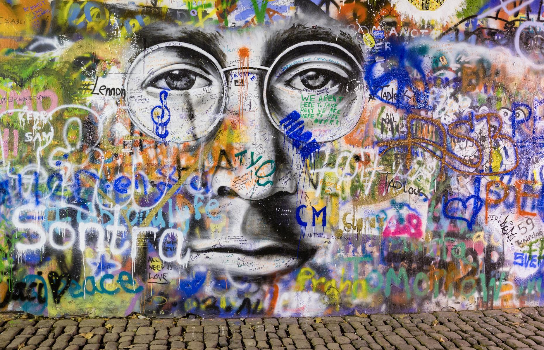 Slide 27 of 31: A long-time haunt for pacifists and dreamers, a wall dedicated to peace, love and John Lennon takes up a quiet corner of Prague. Following the assassination of the Beatles legend in the 1980s, an image of his face was painted on a wall close to the French embassy. Soon after political messages, peace signs and Beatles lyrics were scribbled alongside it, until it was a kaleidoscopic mural that's lasted for decades.