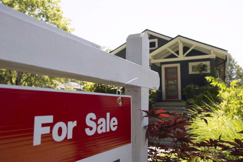 a sign in front of a house: Okanagan real estate boards say that the market isn't showing any signs of cooling with the weather.