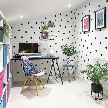 Slide 3 of 10: A small office can feel dark and cramped. To make a space feel bigger and brighter, use recessed LED lighting and playful wallpaper, as shown in this office from @littlesquaresofhome. A cubby wall adds plenty of storage, and freestanding plant stands lighten without bulk.