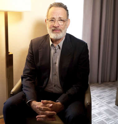 """Tom Hanks wearing a suit and tie sitting in a chair: The novel coronavirus has made its rounds worldwide after first emerging in the Wuhan, Hubei, province in China back in 2019 — and today's biggest stars are not immune. Tom Hanks and Rita Wilson were among the first high-profile names to test positive for COVID-19. On March 11, the Academy Award winner shared the symptoms the couple experienced during their time in Australia, where Hanks was working on pre-production for Baz Luhrmann's Elvis Presley biopic. """"We felt a bit tired, like we had colds, and some body aches,"""" the Forrest Gump actor said of he and Wilson. """"Rita had some chills that came and went."""" On March 16, Us Weekly confirmed that Hanks and Wilson were released from the hospital. The pair, who have been married for 30 years, rented a home in Australia before flying back to the U.S.     Nearly a week after Hanks and Wilson's diagnosis was confirmed, Idris Elba announced that he contracted the virus as well. He revealed via Twitter on Monday that he decided to get tested after learning that an individual he was in contact with tested positive on March 13. The day after speaking out, the English actor shared that Hanks' confession inspired him to speak about his own condition. """"I'm really proud of Tom Hanks, who is also someone in the public eye who came out and said they have it and has been public about it,"""" the Cats actor said in a Twitter livestream video. """"I was really motivated by Tom's move there."""" Scroll down to see all the stars who have tested positive for the novel coronavirus."""