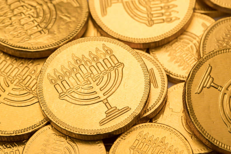 "a coin on a table: Gelt: Another term for money is ""gelt,"" which comes from Dutch, German and Yiddish, which calls the chocolate coins gifted to kids at Hanukkah ""gelt."" This term dates back to 1529."