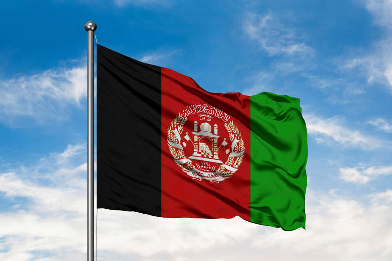 Flag of Afghanistan waving in the wind against white cloudy blue sky.