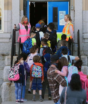 a group of people standing in front of a building:  Students at Stanley Jones School head to classes on Tuesday, Sept. 1, 2020.