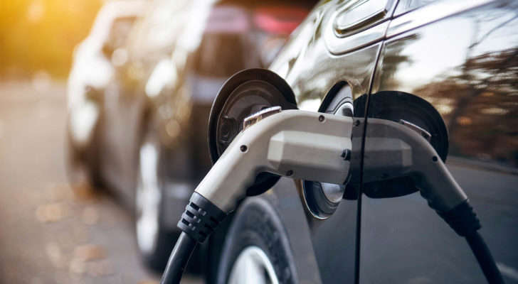 a close up of a motorcycle: A photo of an electric car with the charger plugged in.