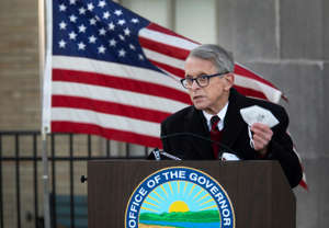 Mike DeWine holding a sign: Gov. Mike DeWine holds his masks up during a press conference at Lunken Airport, Wednesday, Nov. 18, 2020. DeWine traveled across the state to enforce the curfew and the importance of masks and social distancing during the coronavirus pandemic.