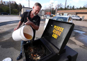 a man holding a sign: Todd Bluechel pours used cooking oil into a recycling receptacle in Louisville, Ky. on Nov. 10, 2020. Bluechel is the v.p. of sales marketing business development for Oil-Tech, a company that recycles used cooking oil.