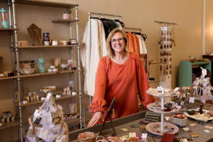 a person sitting at a table with food: Stephanie Deckard, owner of Mad Love Boutique, stands inside her Main Street boutique, Friday, Nov. 20, 2020 in Lafayette.