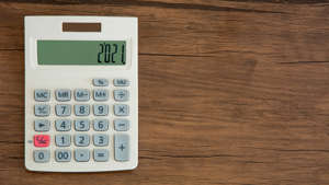 a calculator on a wooden surface: The old saying that nothing is certain except death and taxes is only partly true. Yes, you can certainly expect to pay taxes in 2021, but you almost certainly won't see the same kind of tax return thanks to a number of tax law changes that are coming. Many changes are triggered by inflation, which means the income limits for claiming deductions are increasing. Read on for an update on the tax changes you need to know about to plan for your financial future. Last updated: Nov. 20, 2020