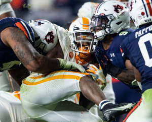 a group of people sitting around a baseball field: Tennessee running back Eric Gray (3) gets sandwiched between Auburn defensive tackle DaQuan Newkirk (44) and Auburn linebacker Zakoby McClain (9) at Jordan-Hare Stadium in Auburn, Ala., on Saturday, Nov. 21, 2020. Auburn defeated Tennessee 30-17.