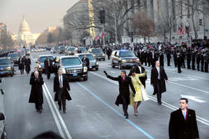 a group of people walking down a busy city street: President Barack Obama and first lady Michelle Obama wave to the crowd during the inaugural parade on Jan. 20, 2009.